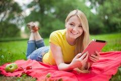 Muchacha que miente en el parque con la tableta Imagen de archivo libre de regalías