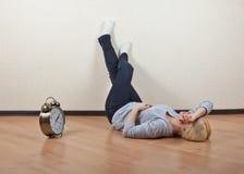 Muchacha que miente en el piso de un cuarto vacío con mis pies para arriba al lado del reloj Foto de archivo libre de regalías