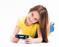 Muchacha que miente en el piso, jugando en la consola fotos de archivo