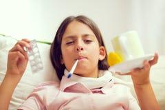 Muchacha que miente en el sofá con un termómetro en su boca Imagen de archivo