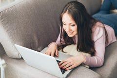 Muchacha que miente en el sofá y que usa un ordenador portátil Fotos de archivo libres de regalías
