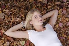 Muchacha que miente en ella detrás en hojas de otoño Fotos de archivo