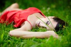 Muchacha que miente en hierba brillante del verano verde Fotografía de archivo