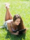 Muchacha que miente en hierba con el ereader Foto de archivo libre de regalías