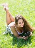 Muchacha que miente en hierba con el ereader Imagenes de archivo