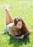 Muchacha que miente en hierba con el ereader Foto de archivo