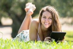 Muchacha que miente en hierba con el ereader Fotografía de archivo libre de regalías