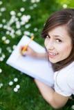 Muchacha que miente en hierba con el libro de trabajo Imagen de archivo libre de regalías