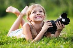 Muchacha que miente en hierba con la cámara profesional en manos Imágenes de archivo libres de regalías