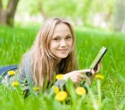 Muchacha que miente en hierba con la tableta y que mira la cámara Imágenes de archivo libres de regalías