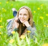 Muchacha que miente en hierba con los dientes de león y que habla en el teléfono Fotos de archivo