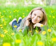 Muchacha que miente en hierba con los dientes de león y que habla en el teléfono Imagenes de archivo