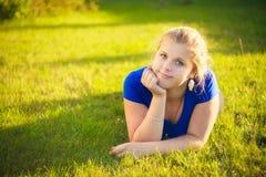 Muchacha que miente en hierba durante día soleado imágenes de archivo libres de regalías