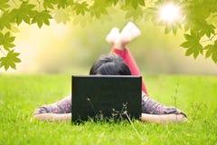 Muchacha que miente en hierba usando el ordenador portátil al aire libre Fotos de archivo libres de regalías