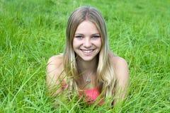 Muchacha que miente en hierba verde Fotos de archivo