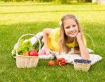 Muchacha que miente en hierba verde con las verduras y la baya Fotografía de archivo libre de regalías