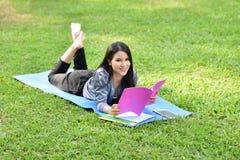 Muchacha que miente en hierba y el libro leído Foto de archivo