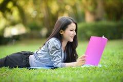 Muchacha que miente en hierba y el libro leído Fotos de archivo libres de regalías