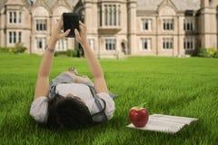 Muchacha que miente en hierba y que manda un SMS con el teléfono móvil Imágenes de archivo libres de regalías