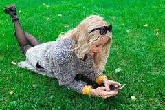 Muchacha que miente en hierba y que sostiene un teléfono Foto de archivo