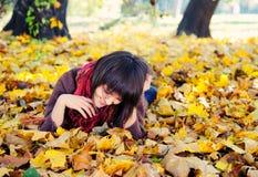 Muchacha que miente en hojas. Imagenes de archivo