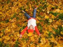 Muchacha que miente en hojas de otoño Fotos de archivo