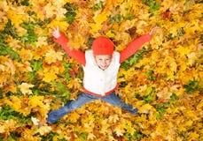 Muchacha que miente en hojas de otoño Imagenes de archivo