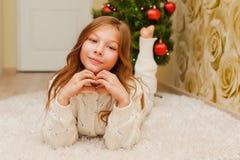 Muchacha que miente en la alfombra, mirando la cámara y la sonrisa Foto de archivo libre de regalías
