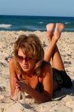 Muchacha que miente en la arena por el mar Imagen de archivo