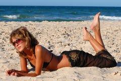 Muchacha que miente en la arena por el mar Imágenes de archivo libres de regalías