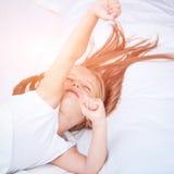 Muchacha que miente en la cama blanca Fotografía de archivo