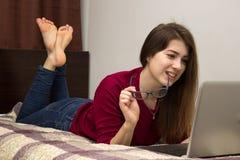 Muchacha que miente en la cama delante del ordenador Fotografía de archivo