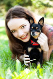 Muchacha que miente en la hierba al lado de un perro Imágenes de archivo libres de regalías