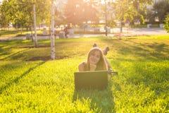 Muchacha que miente en la hierba con la computadora portátil Imagen de archivo libre de regalías