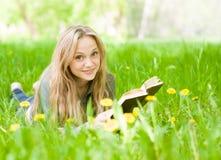 Muchacha que miente en la hierba con los dientes de león que lee un libro Foto de archivo libre de regalías