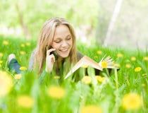 Muchacha que miente en la hierba con los dientes de león que lee un libro y hablar Fotografía de archivo