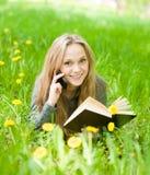 Muchacha que miente en la hierba con los dientes de león que lee un libro y hablar Fotografía de archivo libre de regalías