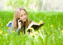 Muchacha que miente en la hierba con los dientes de león que lee un libro y que habla en el teléfono Fotografía de archivo libre de regalías