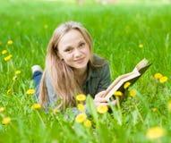 Muchacha que miente en la hierba con los dientes de león que lee un libro y que mira la cámara Imagenes de archivo