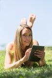 Muchacha que miente en la hierba en prado que goza leyendo el ereader Foto de archivo libre de regalías