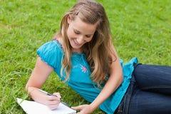 Muchacha que miente en la hierba mientras que escribe Imágenes de archivo libres de regalías