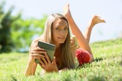Muchacha que miente en la hierba que goza leyendo el ereader Fotografía de archivo