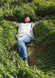 Muchacha que miente en la hierba verde Foto de archivo libre de regalías
