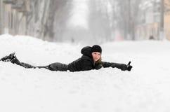 Muchacha que miente en la nieve y que detiene un pulgar Fotografía de archivo