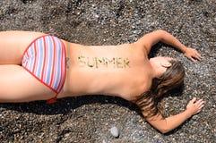 Muchacha que miente en la playa Imagen de archivo