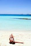 Muchacha que miente en la playa blanca de la arena Fotografía de archivo libre de regalías