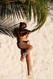 Muchacha que miente en la playa y que lleva a cabo una rama de la palma Fotografía de archivo libre de regalías