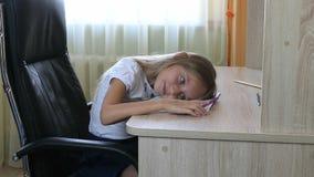 Muchacha que miente en la tabla Estudio cansado chica joven Muchacha caucásica que se acuesta Tiro triste del primer de la cara D Foto de archivo