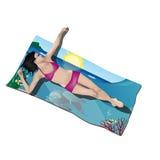 Muchacha que miente en la toalla de playa Fotografía de archivo libre de regalías