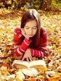 Muchacha que miente en las hojas caidas y que lee un libro Fotos de archivo